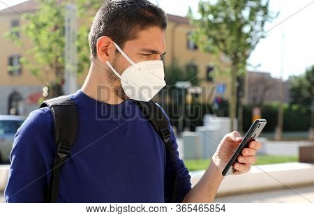 Covid-19 Mobile Application Young Man Wearing Kn95 Ffp2 Mask Using Smart Phone App In City Street To