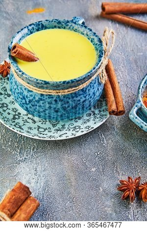 Golden Latte Turmeric Healthy Drink In A Blue Cup. Golden Milk With Turmeric, Cinnamon Sticks, Turme