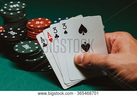 Cards With Two Pairs In Poker In The Hands Of A Gambler On The Background Of Gaming Chips