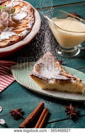 Apple Pie With Cinnamon On The Table, A Piece Of Apple Pie With Condensed Milk On A White Plate. Sli