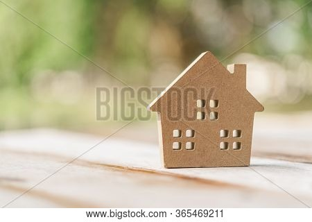 Small Home Model On Wooden Table With Nature Green Bokeh Abstract Background. Family Life And Busine