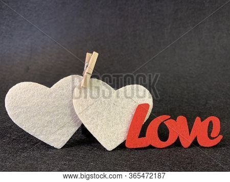 Two Hearts Are Clamped By A Clothespin On A Dark Background. Sign: Love And Fidelity For Two. Concep
