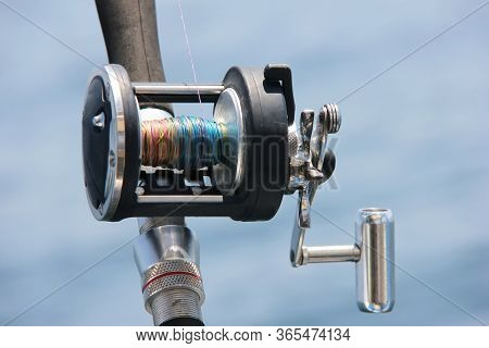 A Close-up Of The Trolling Coil Against The Sea. Fishing And Fishing Supplies.