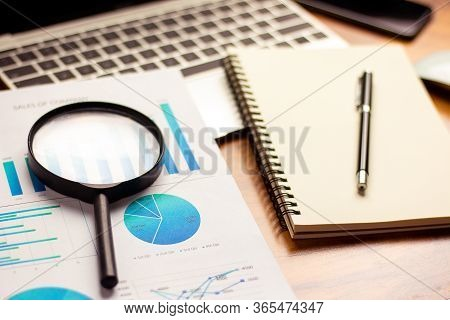 Business Desk With A Notebook, Report Graph Chart, Pen And Tablet On Wooden Table