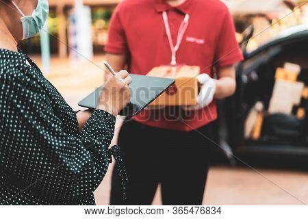 Woman Sign In Digital Mobile Phone After Receiving Parcel From Courier At In Front Of The House,ther