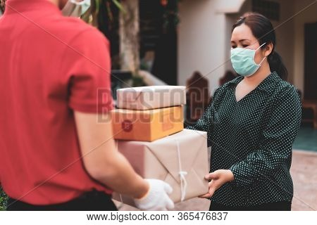 Young Woman Receiving Parcel From Courier Indoors,therefore Must Wear A Mask To Prevent The Spread O