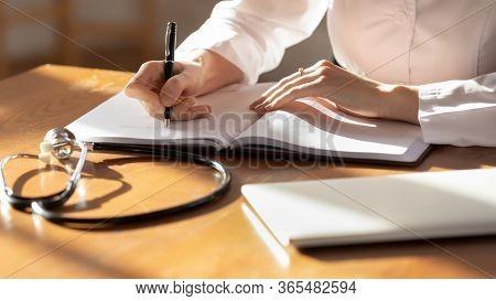 Female Doctor Write In Journal Filling Medical History