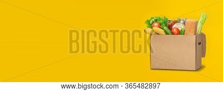 Donation Box With Food On A Yellow Background. Coronavirus Food Delivery. Volunteer Brings A Box Of