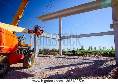 Mobile Crane Is Operating And Worker Is Assembly Concrete Joist In High Place. Height Worker Is Plac