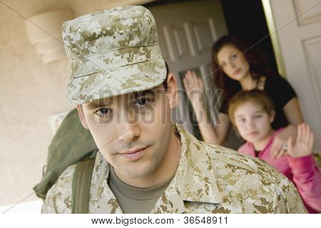 Enlisted man leaving house with family waving in background