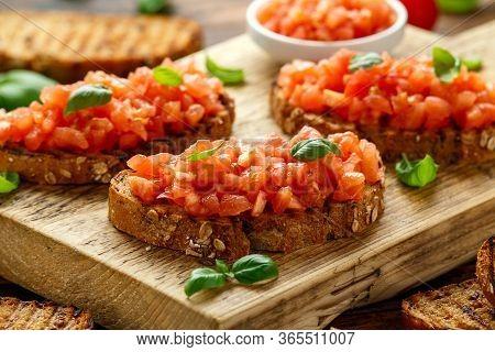Tomato Bruschetta Seasoned With Basil On A Rustic Wooden Board