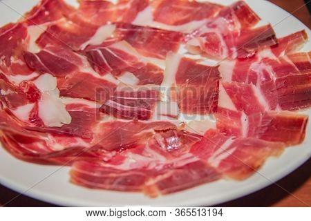 A Plate Of Iberian Ham Cut Very Thin.
