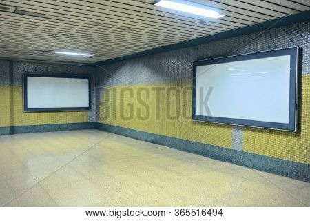 Two Blank Billboards On Yellow And Gray Colored Walls At Subway Corridors