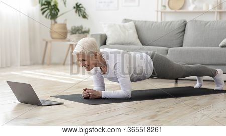 Training At Home. Sporty Senior Woman Doing Yoga Plank While Watching Online Tutorial On Laptop, Exe