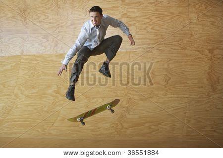 Businessman on skateboard in midair