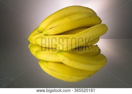 Yellow Bananas On Mirroring Table. Gorizontal Image
