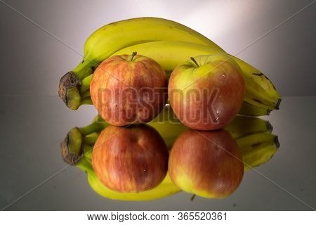 Yellow Bananas And Red Apples On Mirroring Table. Gorizontal Image