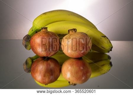 Yellow Bananas And Red Pomegranate On Mirroring Table. Gorizontal Image