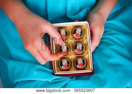 Tambov, Russian Federation - February 14, 2020 Woman Taking Mozart Candy From Candy Box.