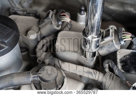Socket Wrench Loosening Screw On Ignition Coil In Car Engine Bay. Mechanic Repair Or Vehicle Mainten