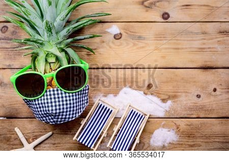 Pineapple With Sunglasses On Wood Background. Creative Minimal Summer Holiday Concept With Miniature