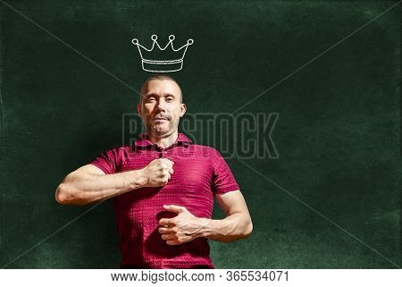 A Smug Man With A Crown On His Head Hits His Chest With His Fist Against The Background Of A Chalkbo