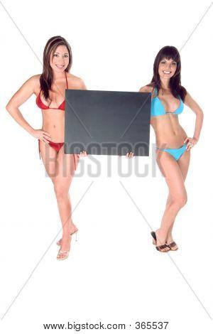 Two Hot Bikini Girls Holding Up Black Sign Board