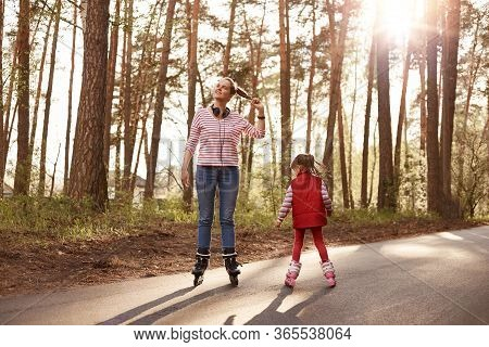 Outside Picture Of Cheerful Energetic Young Female Rollerskating With Her Little Daughter, Enjoying