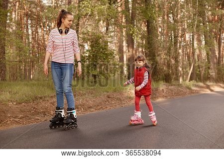 Outdoor Shot Of Young Mummy With Her Cute Daughter Rollerblading In Forest On Asphalt Road, Mom Look