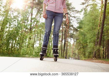 Faceless Portrait Of Slim Female Wearing Jeans And Striped Shirt, Rollerblading On Asphalt Road Surr
