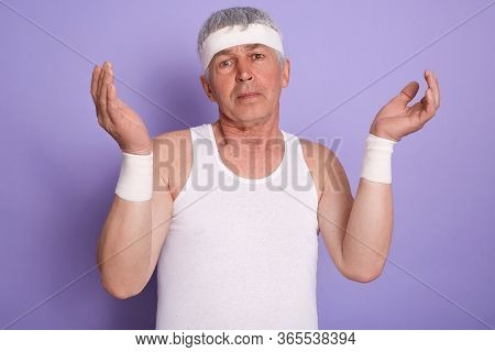 Indoor Shot Of Elderly Man Shrugging Shoulders And Spreading Hands, Showing Helpless Gesture, Posing