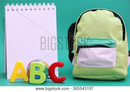 Abc-colored Letters Of The English Alphabet Next To A Toy Globe And A Notepad. School Bag. Back To S