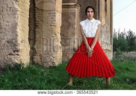 Fashion Model Girl With Brown Hair Against The Background Of An Old, Abandoned Building In A Stylish