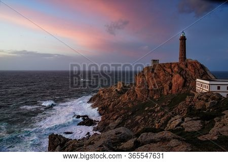 Lighthouse At Cabo Vilan On The Galician Coast In A Colourful Sunset And With The Sea In A Rage. The
