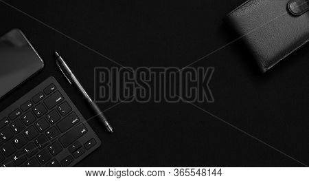 Flat Lay Composition With Black Pen, Computer Keyboard, Smartphone And Leather Wallet On Dark Black