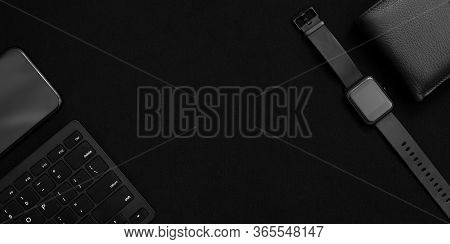 Flat Lay Composition With Black Computer Keyboard, Smart Watch, Smartphone And Leather Wallet On Dar