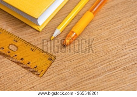 Yellow Notebook, Yellow Pen, Yellow Pencil And Yellow Ruler On A Wooden Table Surface. Stationery Of