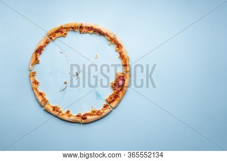 Pizza Pepperoni Leftovers Top View On A Blue Background. Homemade Pizza Remainings And Traces Of Gre
