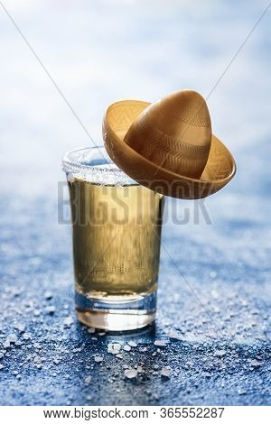 Shot Of Tequila With Salt On A Blue Table With Backlight. Glass Of Gold Tequila With A Small Sombrer