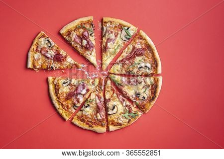 Pizza Prosciutto Sliced In Eight On A Red Table. Homemade Delicious Pizza. Italian Pizza With Fresh