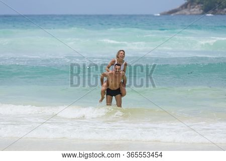 Happy holiday moment, lover couple play together, enjoy the turquoise blue tropical sea at the beach