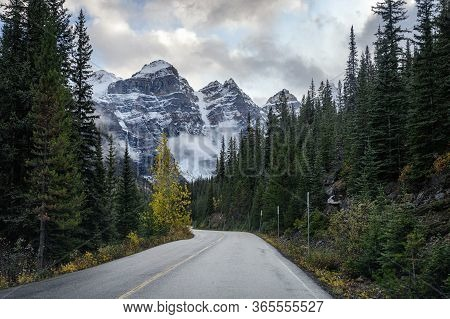 Driving On Road In Pine Forest With Rocky Mountains At Moraine Lake, Canada