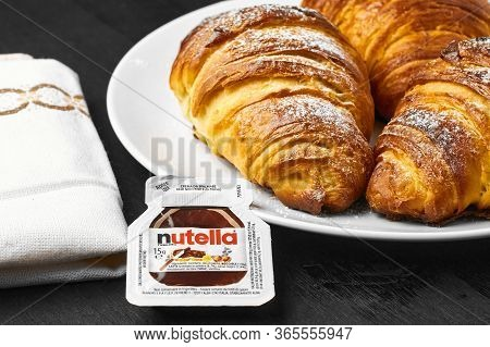 Freshly Baked Croissants With Nutella On A White Plate Near Serviette On A Black Background. Traditi