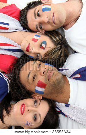 Four French sports fans laying together