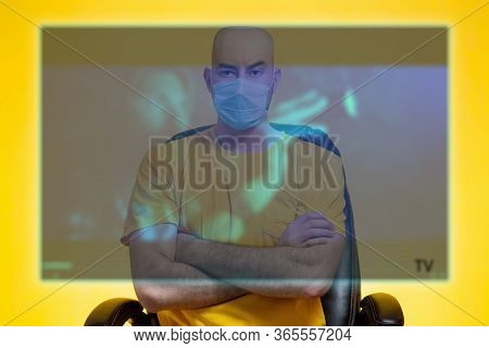 The Bald Man In The Medical Mask Crossed His Arms In Front Of The Transparent Digital Tv Screen. Yel