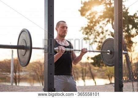 Man With Barbell Outdoor Gym On Nature In Park. Young Adult Caucasian Athlete Lifts A Barbell With A
