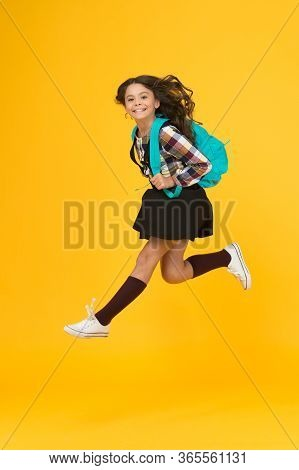 Moving With Haste. Energetic Child In Midair Yellow Background. School Girl In Energetic Jump. Back