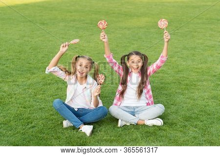 Confectionery. Sweet Caramel. Happy Children Hold Candy Sit Grass. Candy Shop. Lollipop Treats. Cand