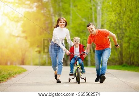 Family Activities Summer Day. Happy Mom And Father Learning Little Kid Son To Ride Bicycle