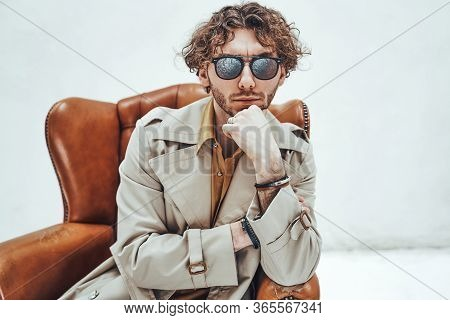 Thoughtful And Daring, Young Male Model Posing In A Studio For The Photoshoot Wearing Fashionable Tr
